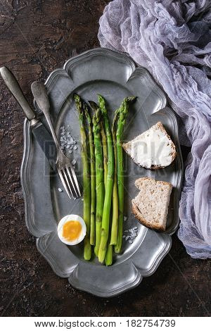 Cooked green asparagus with half boiled egg and sliced bread served with sea salt and cutlery on vintage metal plate with gauze textile over brown texture background. Top view, fine dining
