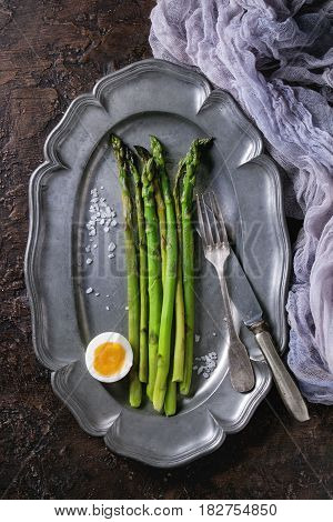 Cooked green asparagus with half boiled egg served with sea salt and cutlery on vintage metal plate with gauze textile over brown texture background. Top view, fine dining