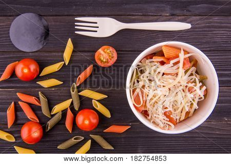 A penne tomato with parmesan, multi-colored macaroni and cherry tomatoes