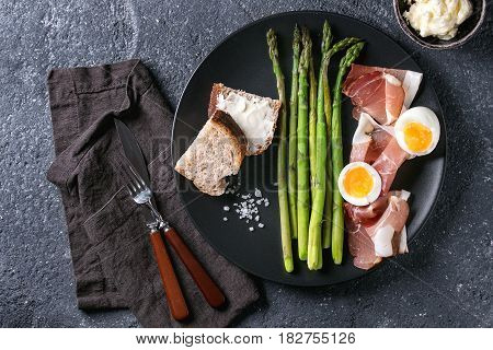 Cooked green asparagus with half boiled egg, sliced bread, butter and ham bacon served with sea salt and cutlery on black ceramic plate over dark stone texture background. Top view, fine dining