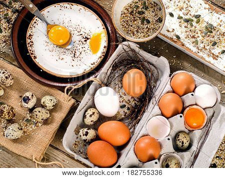 Chicken and quail eggs in egg box on rustic wooden background. Top view