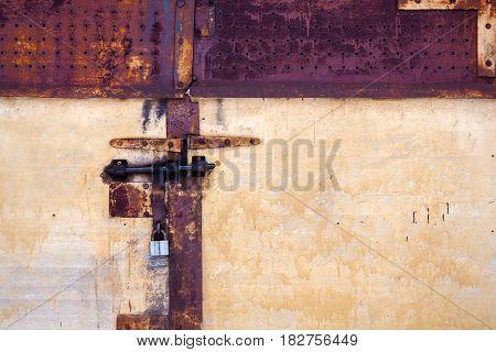 Grunge old rusty metal door with padlock