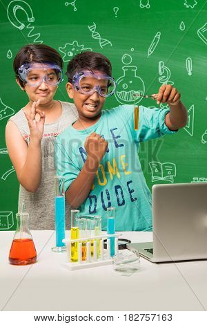 2 little indian kids doing science experiment or chemistry experiment in classroom with safety eye glasses on standing over green chalkboard background with science doodles drawn over it