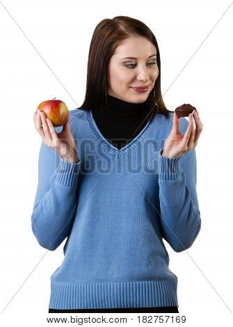 Young woman deciding between an apple and a muffin, isolated on white