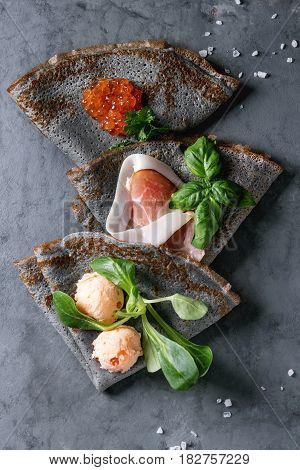 Black pancakes crepes with variety of salt filling red caviar, ham, fish salmon pate, green salad over gray texture metal background. Top view
