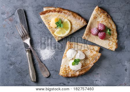 Sweet crepes pancakes with different fillings fresh raspberries, lemon curd, mascarpone cheese, mint, sugar powder with vintage cutlery over gray blue metal texture background. Top view with space