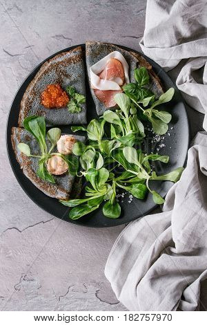 Black pancakes crepes with variety of salt filling red caviar, ham, fish salmon pate, green salad with textile linen napkin over gray texture background. Top view