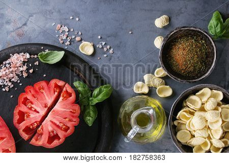 Homemade raw uncooked pasta with whole and sliced organic tomatoes Coeur De Boeuf, salt, seasoning, olive oil and basil over blue gray metal texture background. Top view with space. Italian cuisine