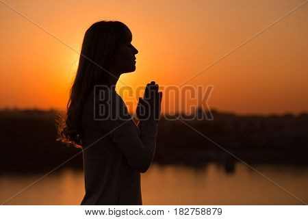 Silhouette of a woman meditating at the sunset.