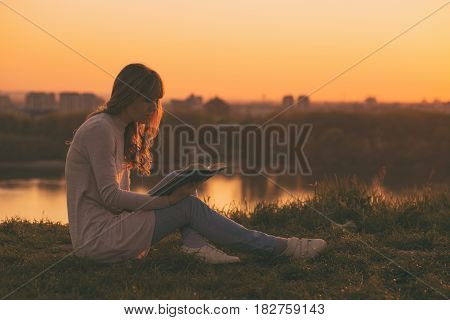 Woman enjoys reading a book with a sunset over the city.