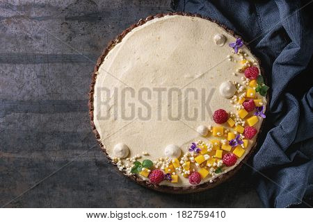 Homemade chocolate tart decorated by mango, raspberries, mint, puffed rice and edible flowers served with blue textile over dark old metal background. Top view with space. Comfort food concept.