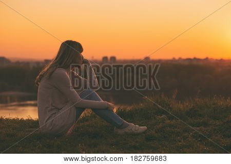 Sad woman sitting at the sunset and thinking.