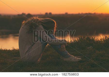 Photo of sad woman sitting at the sunset.