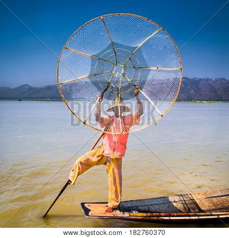 INLE , MYANMAR-MARCH 4, 2017: Traditional Burmese fisherman standing on one leg and holding the basket to catches fish at Inle lake on March 4, 2017,  Myanmar. (Burma)