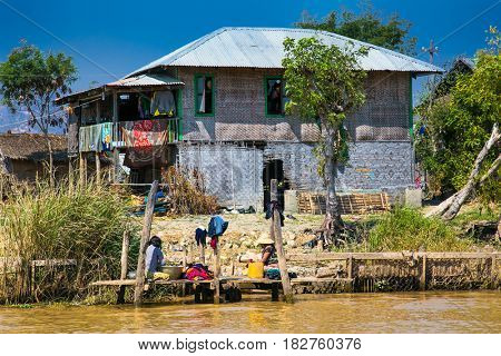 Inle Lake, Myanmar - March 4, 2017 : Two burmese women washing laundry by hand in a canal at the Inle Lake on March 4, 2017, in central Myanmar. (Burma)