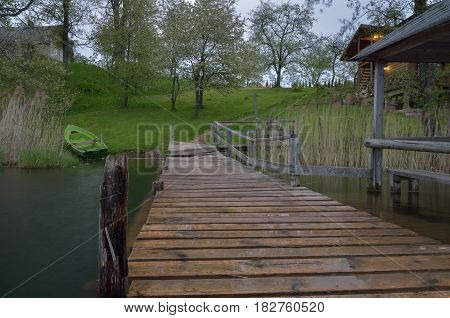 Old pier in the lake near the house in countryside.