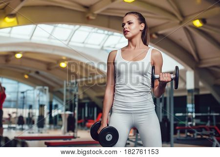 Beautiful girl doing exercises with dumbbells in the gym dressed blank white tank-top and tights
