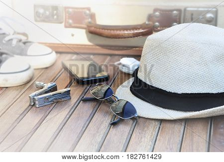 straw hat sunglasses phone shoes and suitcase on wooden background