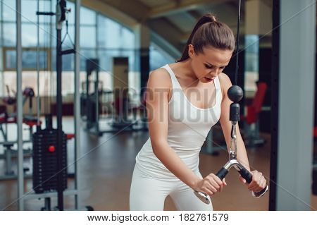 Beautiful girl doing exercises on the simulator in the gym dressed blank white tank-top and tights.