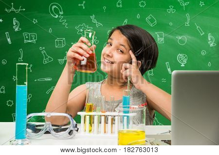 Kids and Science concept - Cute Indian little girl busy doing science or chemistry experiment with test tube and flask with safety eye glass over green chalkboard background with science doodles drawn