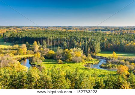 A bright natural landscape in the fall season. A view over the forest, meadows and the river in Southern Estonia.