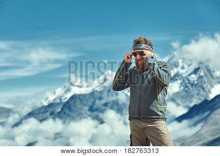 hiker at the top of a pass Puts on sunglasses and enjoy sunny day in Alps. Switzerland, Trek near Matterhorn mount.