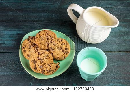 A plate of chocolate chips cookies on a dark blue background, with a glass and jar of milk and copy space