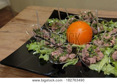 Tuna Fish Portions with Vegetable Condiment Green Salad and Orange Fruit on Black Dish