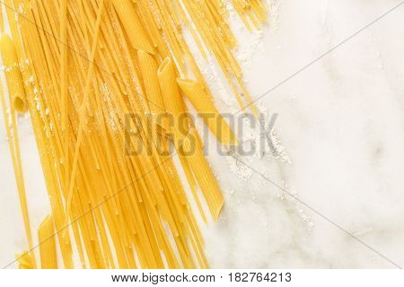 A closeup of spaghetti and penne pasta with traces of flour, shot from above on a white marble texture with a place for text