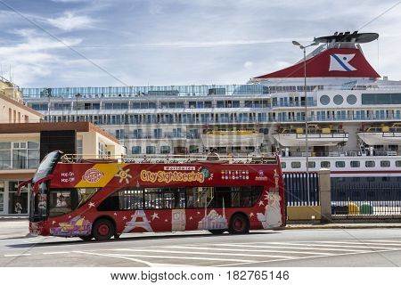 Cadiz Spain- April 1: Brightly decorated sightseeing double-decker open top bus in Cadiz takes visitors to all the major tourist attractions near the port in the background a Norwegian ferry docking at the pier Take in Cadiz Andalusia Spain