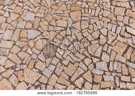 Paving blocks made of asymmetrical stone. The stone pavement as the background texture Stone block road pavement