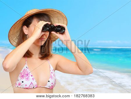 Young woman as a coastguard with binocular watching on beach. Summer in tropical paradise. Travel and insurance concept.