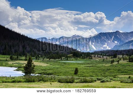 Mountain valley in Northern Colorado with mountain peaks lakes and streams.