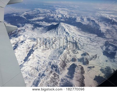 View from airplane window snowy mountains below