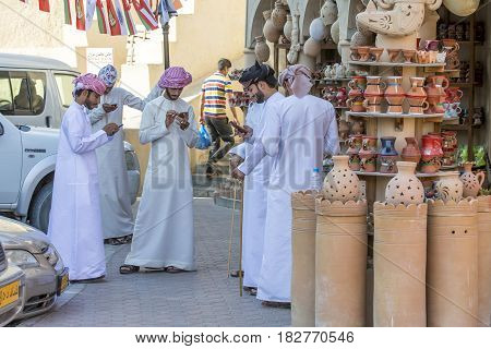 Omani Men At A Market, All In Their Mobile Phones Texting