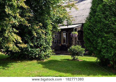 Tree surrounded farmhouse courtyard with a green lawn.