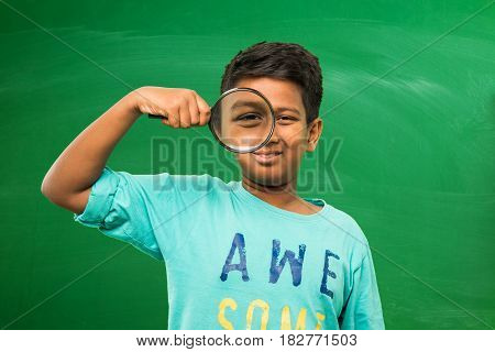 little indian boy holding magnifying glass standing isolated over green chalkboard background