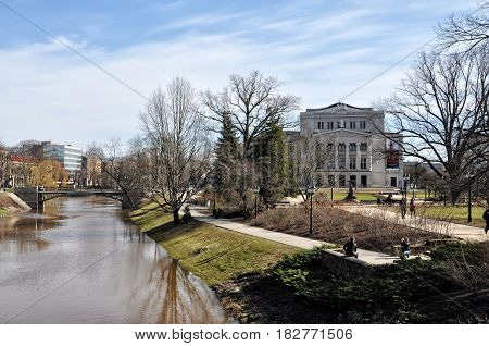 RIGA LATVIA - APRIL 13 2011: City Canal and the Opera Theatre during the first days of spring after snowmelt.