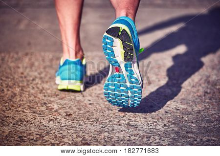 Running athlete during training outdoors in the summer on a sunny day.