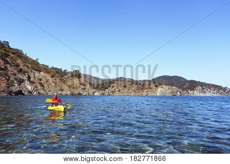 Travel by canoe along the sea on a sunny day.