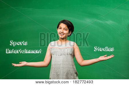 indian school kid or boy pulling hair in sadness or distress because of study pressure or competition, standing isolated over green chalkboard background