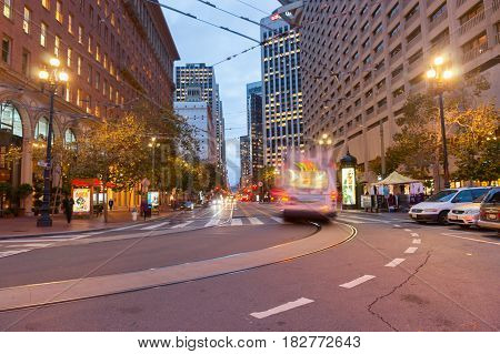 San Francisco, USA  - October 29, 2016; Market Street with it's tram lines and buildings at dusk with street lights and blurred light trails from moving vehicles San Fransisco streets and architecture