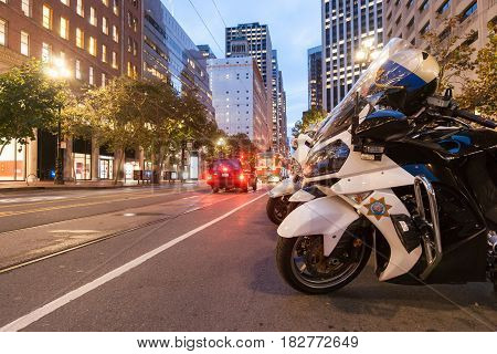 San Francisco, USA  - October 29, 2016; Group highway patrol motorcycles parked on Market Street with it's tram lines and buildings at dusk with street lights and blurred light trails from moving vehicles San Fransisco