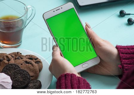 Beautiful girl holding a smartphone in the hands of a green screen green screen, hand of man holding mobile smart phone with chroma key green screen on white background