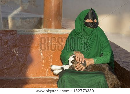 Omani Woman In A Market With A Baby Goat