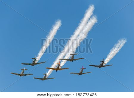 EDEN PRAIRIE MN - JULY 16 2016: Seven AT6 Texan airplanes fly overhead in clear sky with smoke trails at air show. The AT6 Texan was primarily used as trainer aircraft during and after World War II.