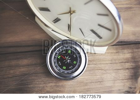 Compass and watch on wood texture background