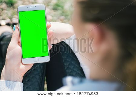 Girl with smartphone in hands with mock up green screen of blank screen sits in park on open space, screen for content integration. Hands holding gadget on blurred backdrop,