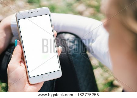 Girl with smartphone in hands with mock up green screen of blank screen sits in park on open space, screen for content integration. Hands holding gadget on blurred backdrop, front