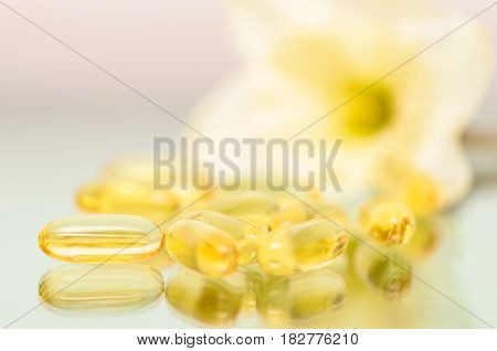 Clouseup of fish oil capsules on flower background. Macro of vitamins dietary supplements.